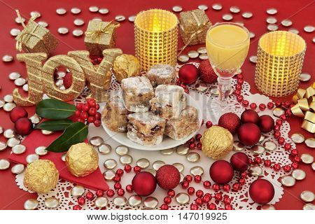 Christmas sweet food with stollen cake bites, candles, gold glitter joy sign, advocaat egg nog, holly and decorations on a red background.