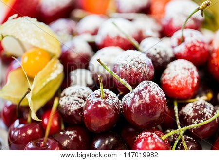 food, dessert and summer concept - close up of dish with sugared fruits or cherries