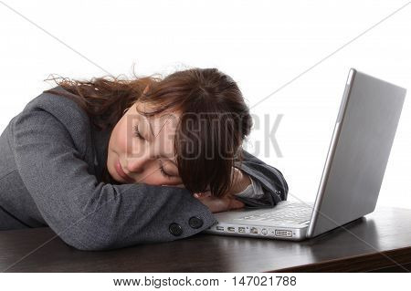 Tired woman sleeping in front of the computer isolated on white