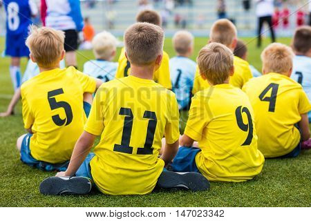 Children soccer football team at the sport stadium. Boys sitting on football pitch during school soccer tournament for youth teams