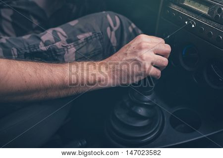 Male driver hand shifting gear manually selective focus