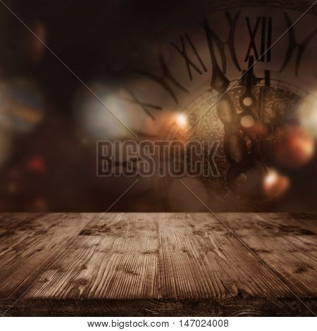 Wooden table in front of a festive background with a clock