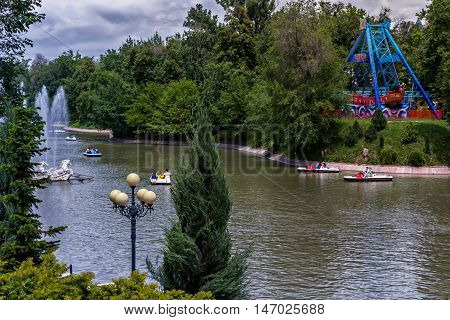 Almaty, Kazakhstan - May 22, 2016. Rest on a lake in a city park. Central City Park of the city of Almaty - one of the biggest in the city. Its area is 42 hectares. It was founded in 1856. The park created two artificial pond. At one installed water park