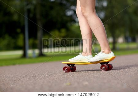 skateboarding, leisure, extreme sport and people concept - close up of teenage girl legs riding short modern cruiser skateboard on road in park