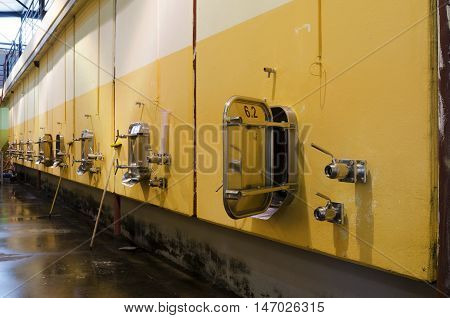 Wall in Bulgarian winery with stainless steel fermentation vessels