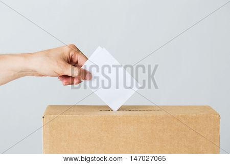 voting, civil rights and people concept - male hand putting his vote into ballot box on election