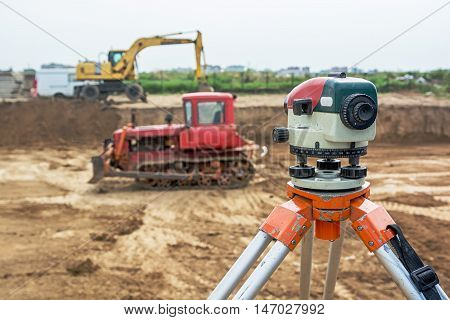 Theodolite on tripod at construction site with excavators and dozers on a background