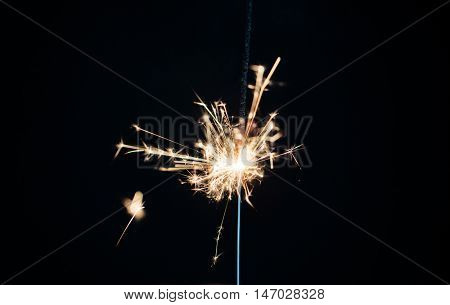 christmas, holidays, new year party and pyrotechnics concept - sparkler or bengal light burning over black background