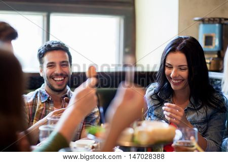people, leisure, friendship and communication concept - happy friends drinking beer and eating snacks at bar or pub