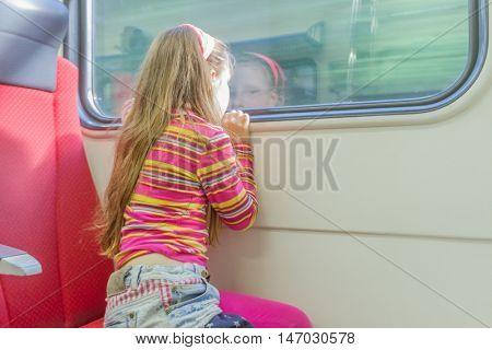 young little caucasian girl traveling by train and looking through window