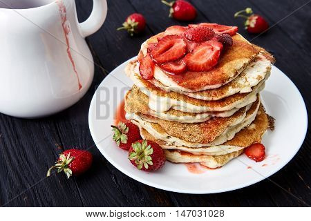 American pancakes with sliced strawberries and strawberry jam on a white plate. Delicious hot breakfast for the whole family. Black wood background, a white pitcher and fresh strawberries near it