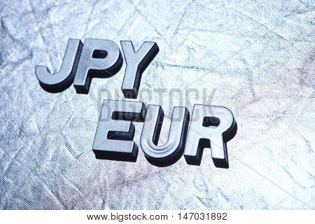 letters on silver background spelling JPY/EUR