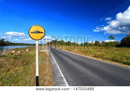 Speed bump sign beside asphalt road and blue sky.