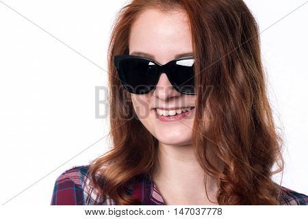 Smiling girl in sunglasses. Close-up portrait of a young woman in a checkered shirt isolated on a white background