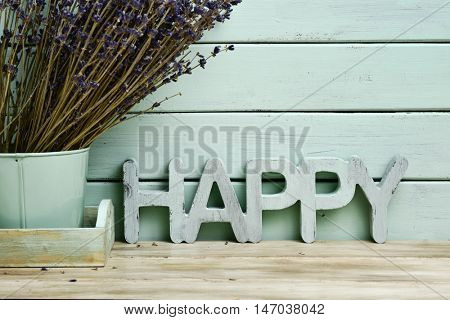 closeup of the three-dimensional word happy and a bunch of lavender flowers in a flower pot, against a rustic pale blue background