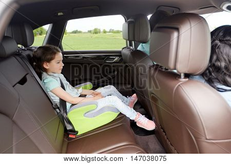 family, transport, road trip and people concept - happy little girl in safety seat driving in car