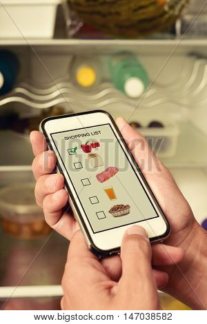 young man making his shopping list in his smartphone, with pictures of different products shot by myself in its screen, in front of the fridge