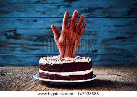 a red velvet cake topped with a bloody hand for halloween, on a rustic wooden surface, against a blue wooden background