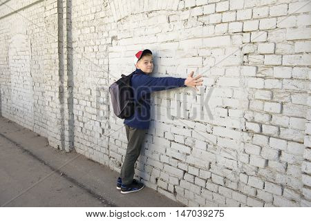 boy with a backpack against the background of an old wall. Serious look.