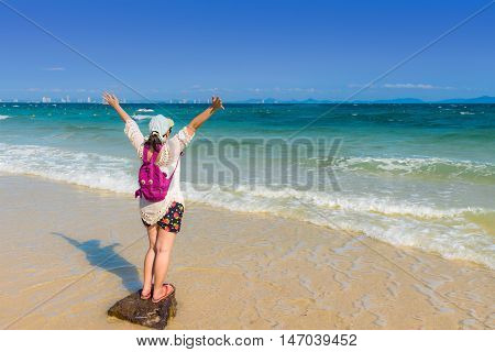 Happy young woman spreading hand on the beach for relaxing.