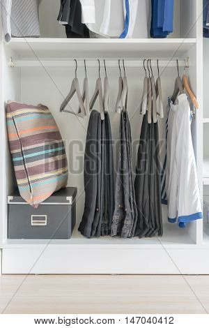 Clothes Hanging On Rail In Modern White Wardrobe