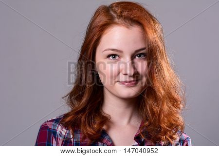 Smiling girl looking at the camera. Close-up portrait of a young woman in a checkered shirt on a gray background