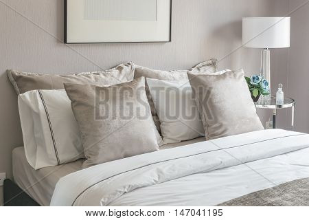 Classic Bedroom Style With Set Of Pillows On Bed And White Lamp On Table