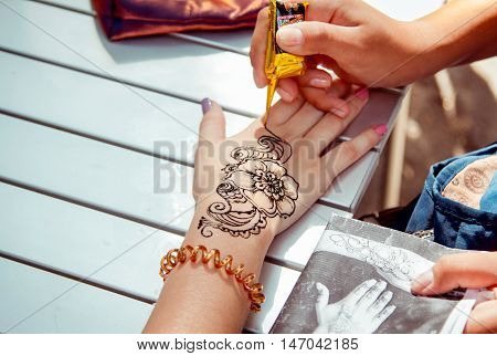 Zaporizhia/Ukraine- September  3, 2016: Charity festival for children - City of professions . Applying temporary henna tattoo activity.  Closeup teen girl arm - flower ornament painting process.