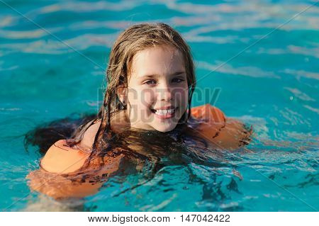 Caucasian child girl in swimming pool. Girl smiling, looking into camera. Child with water wings in swimming pool. Kids learning to swim.