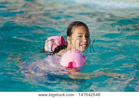 Asian child girl in swimming pool. Girl smiling, looking into camera. Child with water wings in swimming pool. Kids learning to swim.