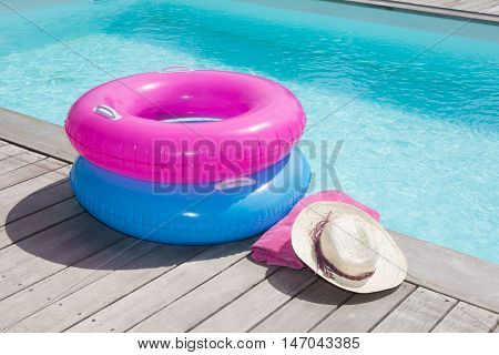 Colorful Towel And Blue And Pink Buoy Near The Pool