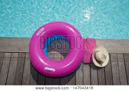 Pink buoy on the pool on wooden deck