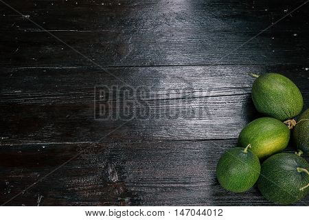 Oval green melons in the corner of the dark wood surface