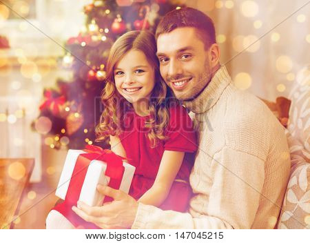 family, christmas, x-mas , happiness and people concept - smiling father and daughter holding gift box