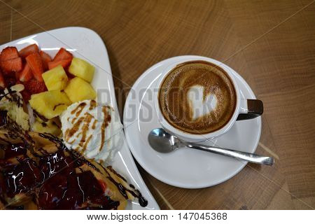 Cup of foamy cappuccino and waffles with fruit and whipped cream