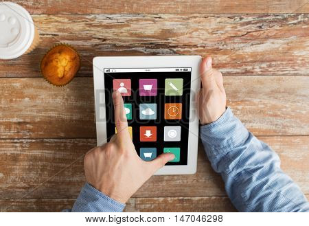 business, media, people and technology concept - close up of male hands with menu icons on tablet pc computer screen, muffin and coffee cup on wooden table