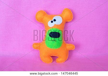 Orange felt toy bear on pink background