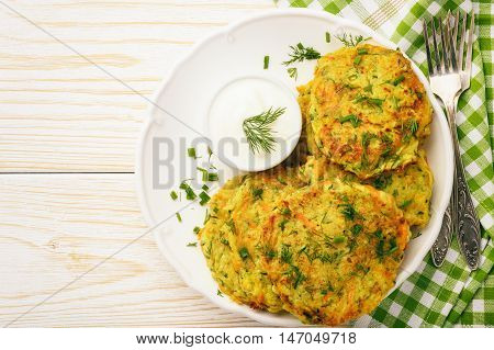 Fritters with zucchini and carrots on white wooden background.