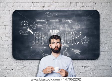 Thoughtful bearded businessman with coffee cup in hands standing against chalkboard with business sketch. Startup concept