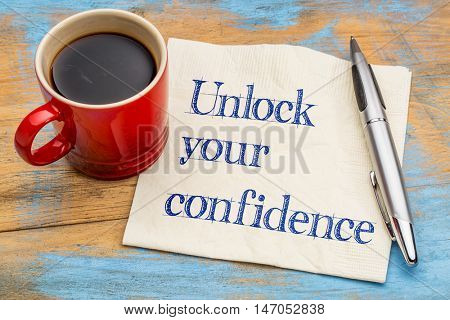 Unlock your confidence advice  or reminder - handwriting on a napkin with a cup of espresso coffee