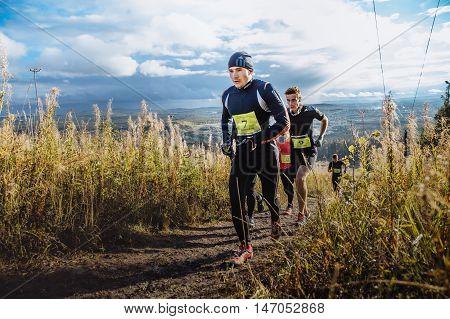 Revda Russia - September 10 2016: group of men runners marathon running up mountain on blue sky background during marathon Vertical kilometer