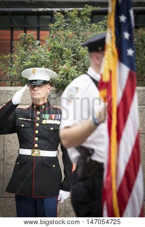 NEW YORK-SEPT 9 2016: A US Marine salutes the American Flag at the NYPD Emerald Society Pipe and Drums 9/11 Memorial Procession on the 15th anniversary of the terror attacks.