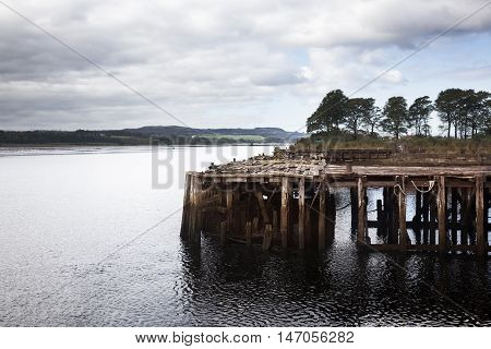 A old pier in wreckage of an abandoned ship anchored in Bowling. Scotland