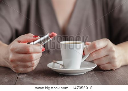 Woman holding cup of espresso and lipstick