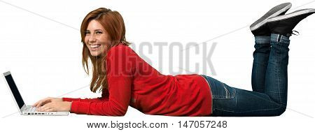 Redheaded female lying in front of a laptop