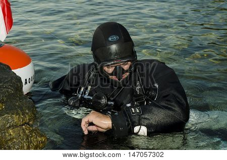 Side mount diver watching his computer before diving