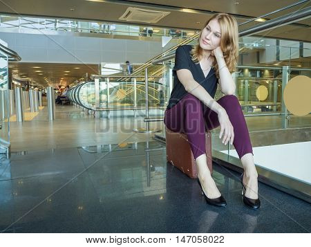 Attractive young woman sitting on a suitcase in the airport lobby. aircraft flight Waiting. Flight cancellation.