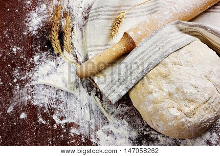 Homemade pizza or bread dough with rolling pin on a linen napkin on the wooden table.