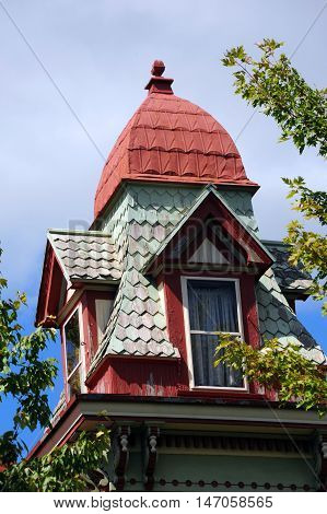 Queen Ann Victorian home has square turret with dome top. Wooden shingles are painted pastel green and dormer is red.
