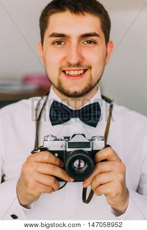 Young handsome looking photographer with camera posing indoors. Close up.